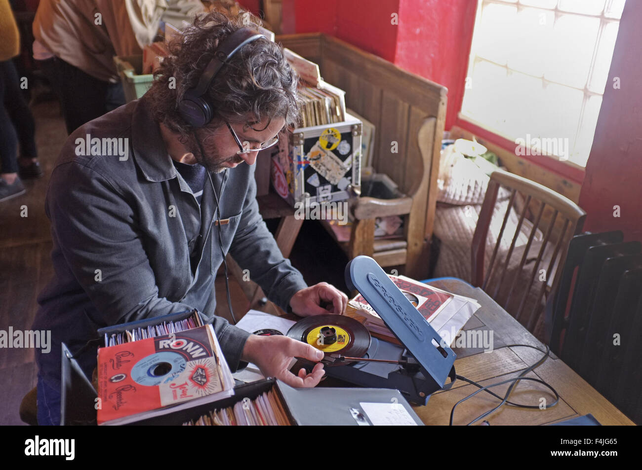 A record collector at a record fair looking through records. He checks out 45's (singles) on a portable turntable. - Stock Image