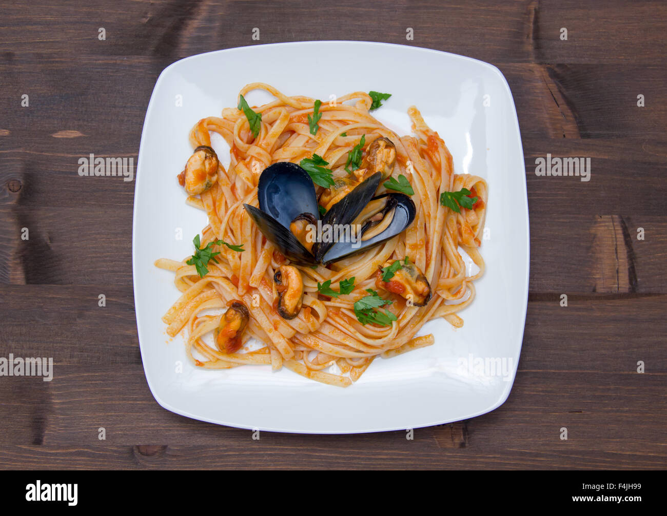 Pasta with mussels on the plate on wooden table top view Stock Photo