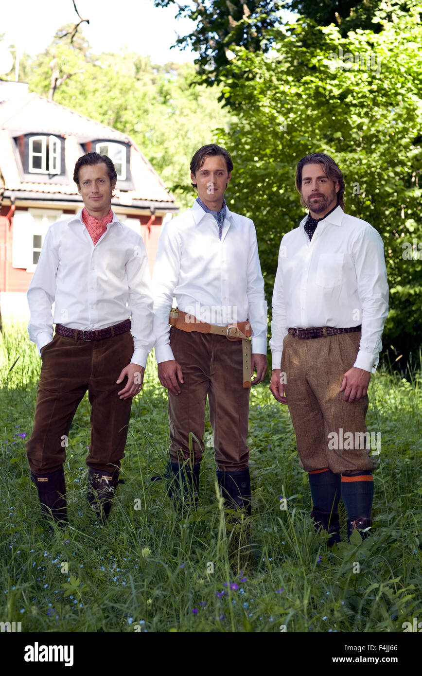 Three midadult men posing in front of house - Stock Image