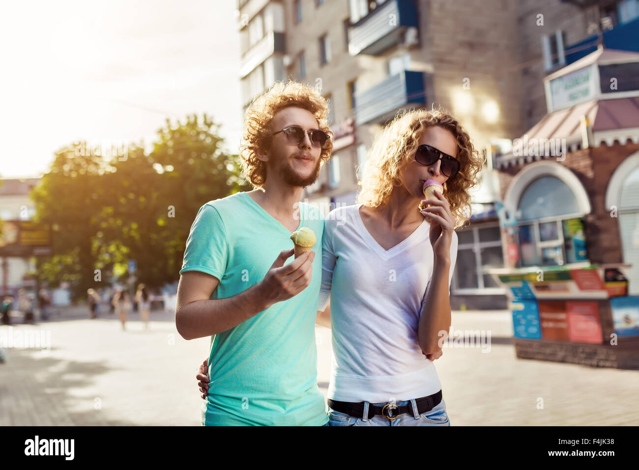 Handsome young couple walking together and licking ice cream - Stock Image