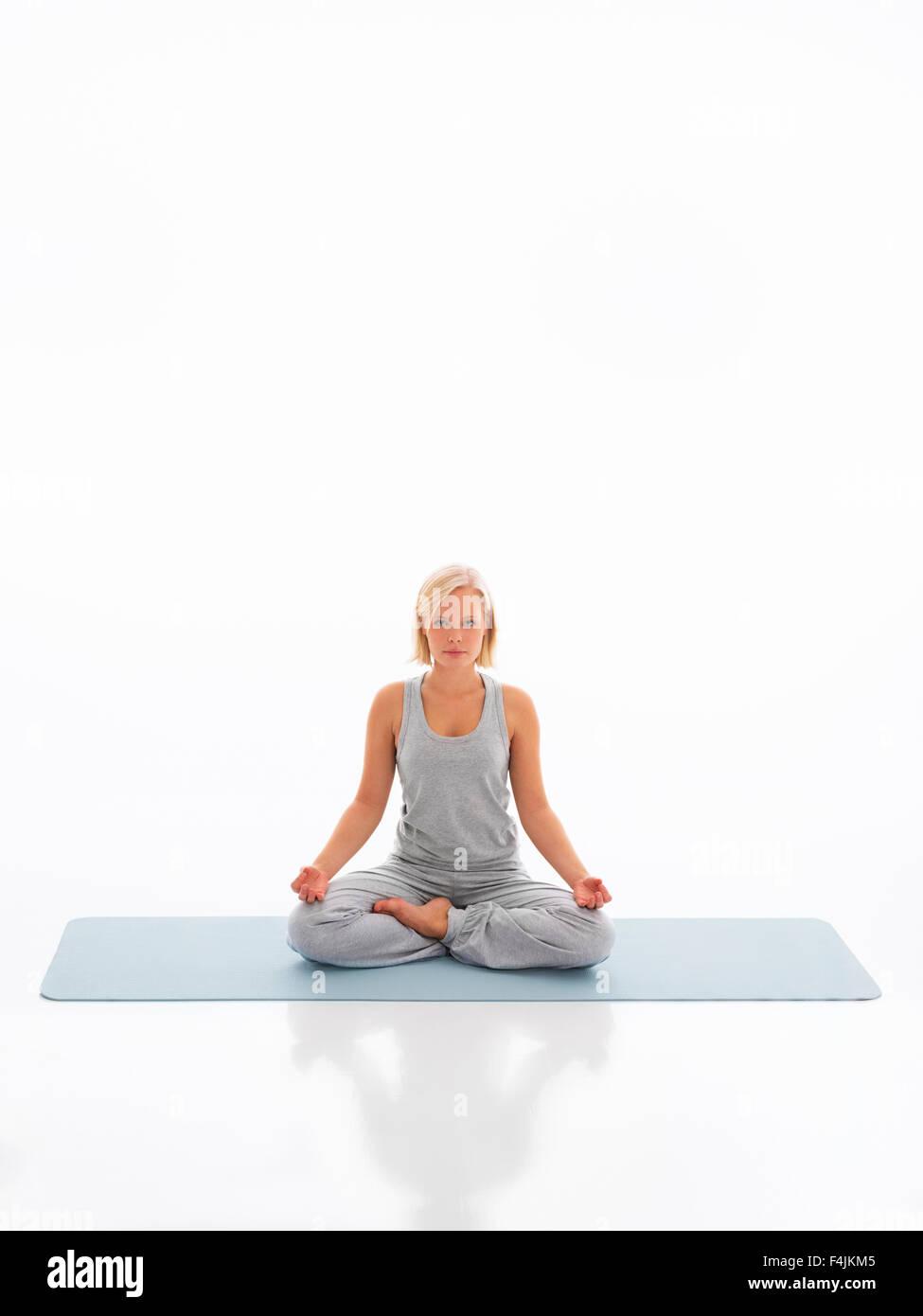 Studio portrait of teenage girl doing yoga Stock Photo