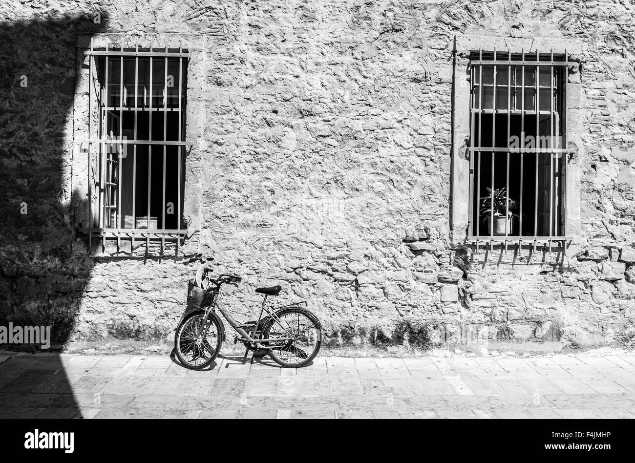 Bicycle leaning against house wall. Black and white photo - Stock Image