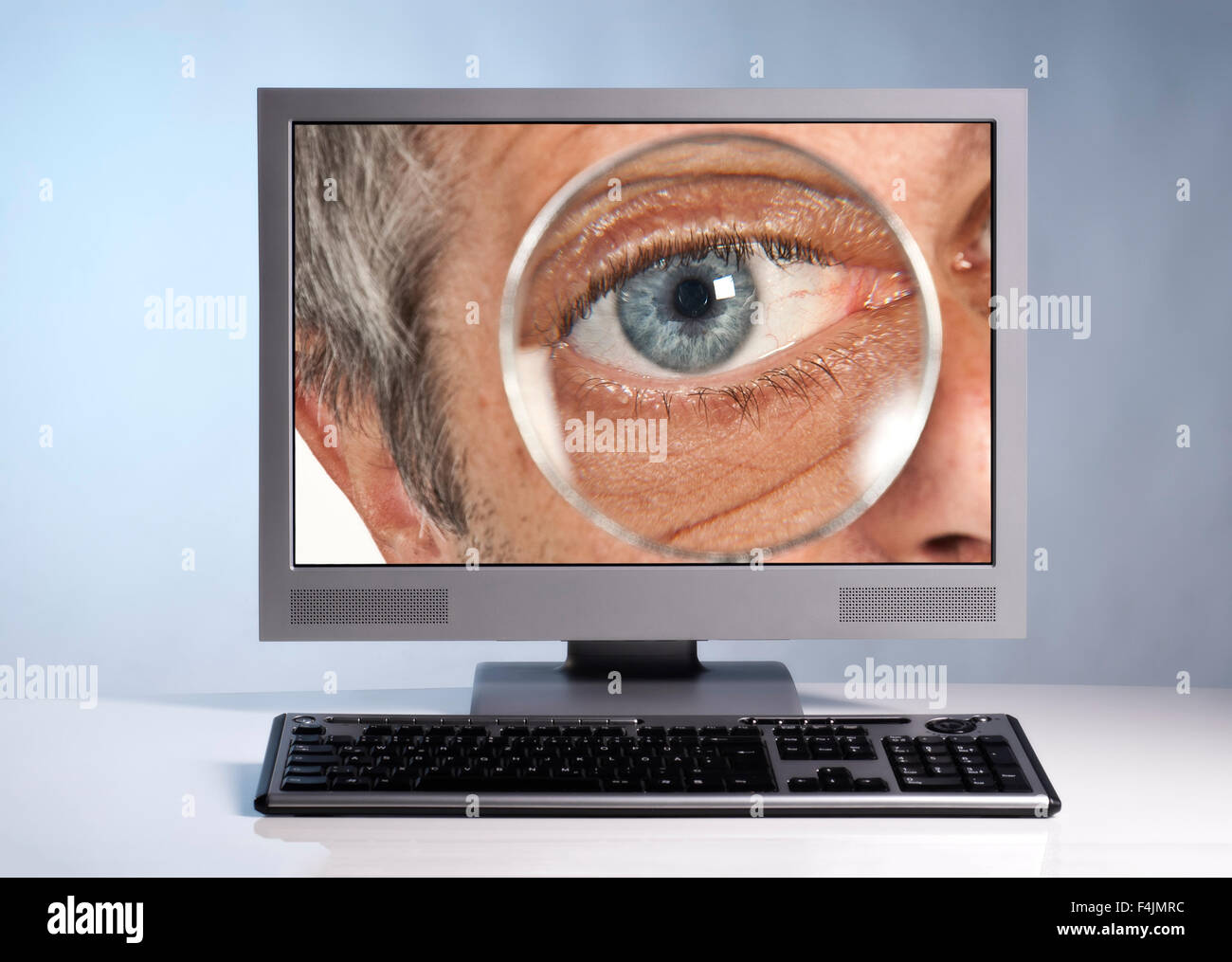 Monitor with eye and magnifier - Stock Image