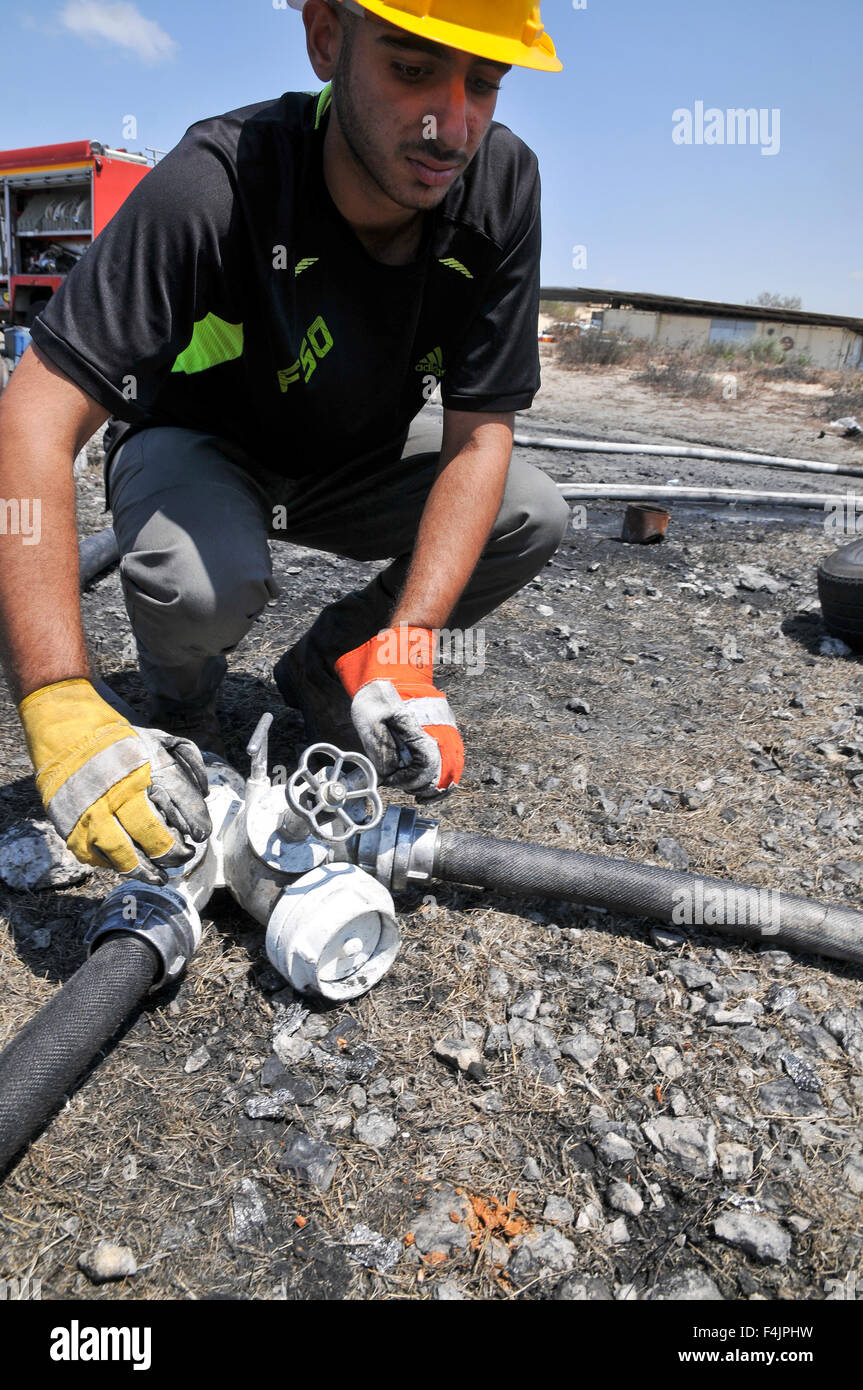 Fireman connects hoses to a water source - Stock Image