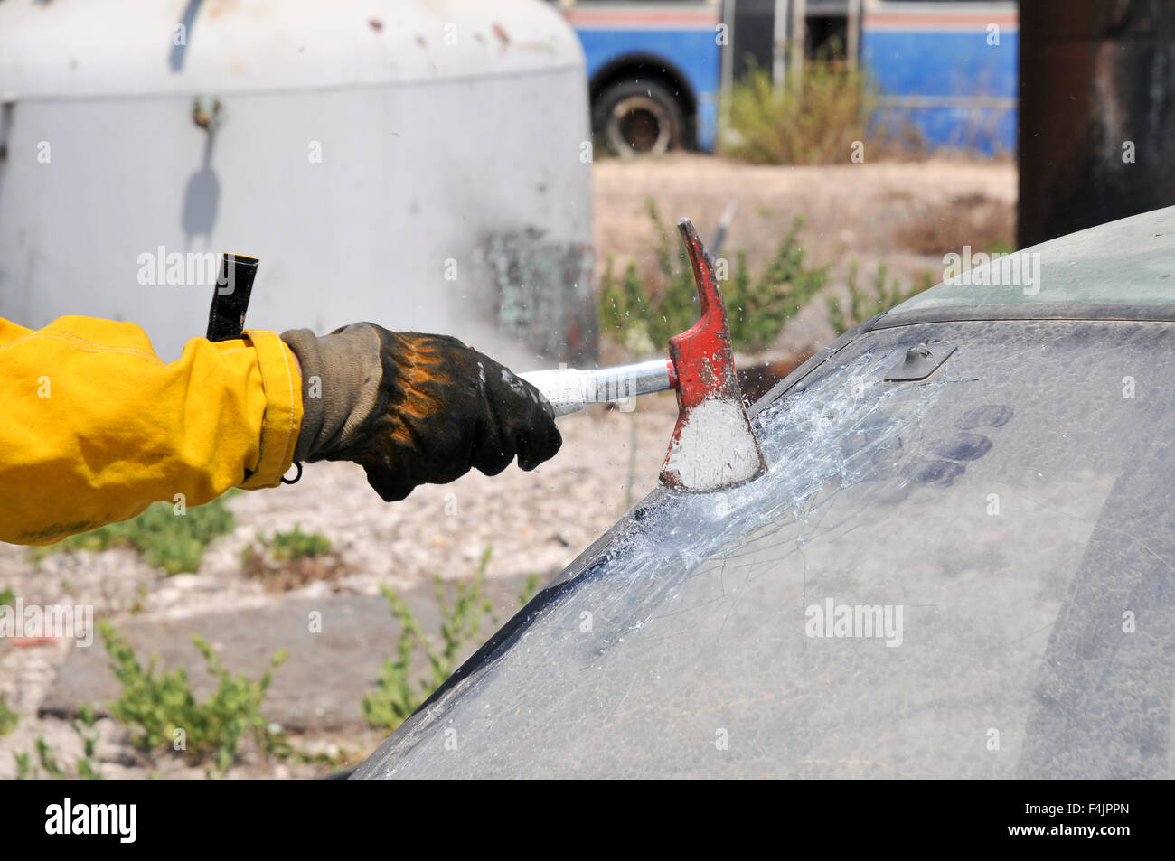 Firefighter uses an axe to break the front windshield of a car to rescue the trapped driver and passengers - Stock Image