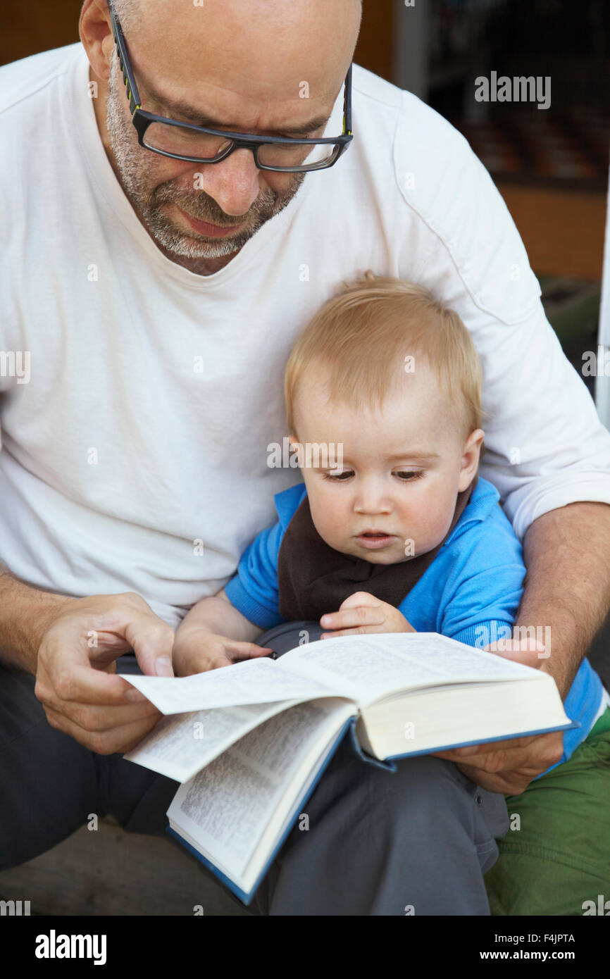 Grandfather reading encyclopaedia to grandson - Stock Image