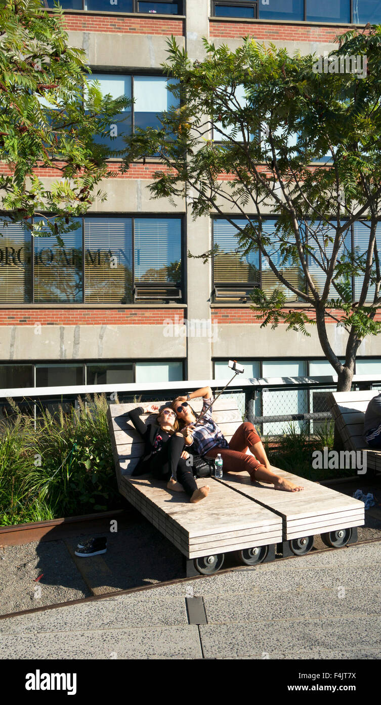 Two caucasian women using a selfie stick to take a picture of themselves relaxing and sunbathing on the High Line - Stock Image