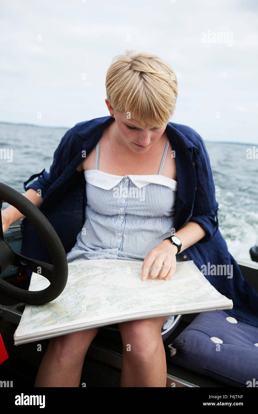 Young woman reading nautical chart - Stock Image