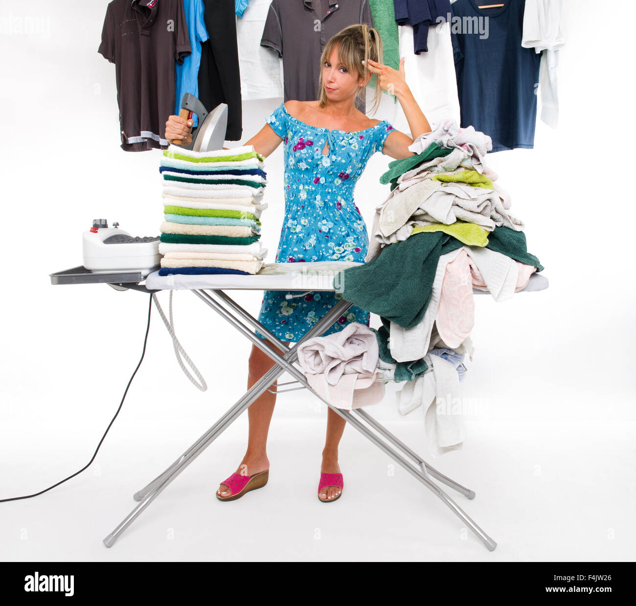 Woman with hands makes the gesture of shooting himself while ironing on board many clothing - Stock Image