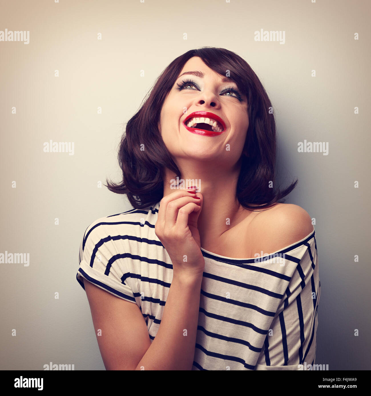 Happy loudly laughing young casual woman looking up. Vintage closeup portrait - Stock Image