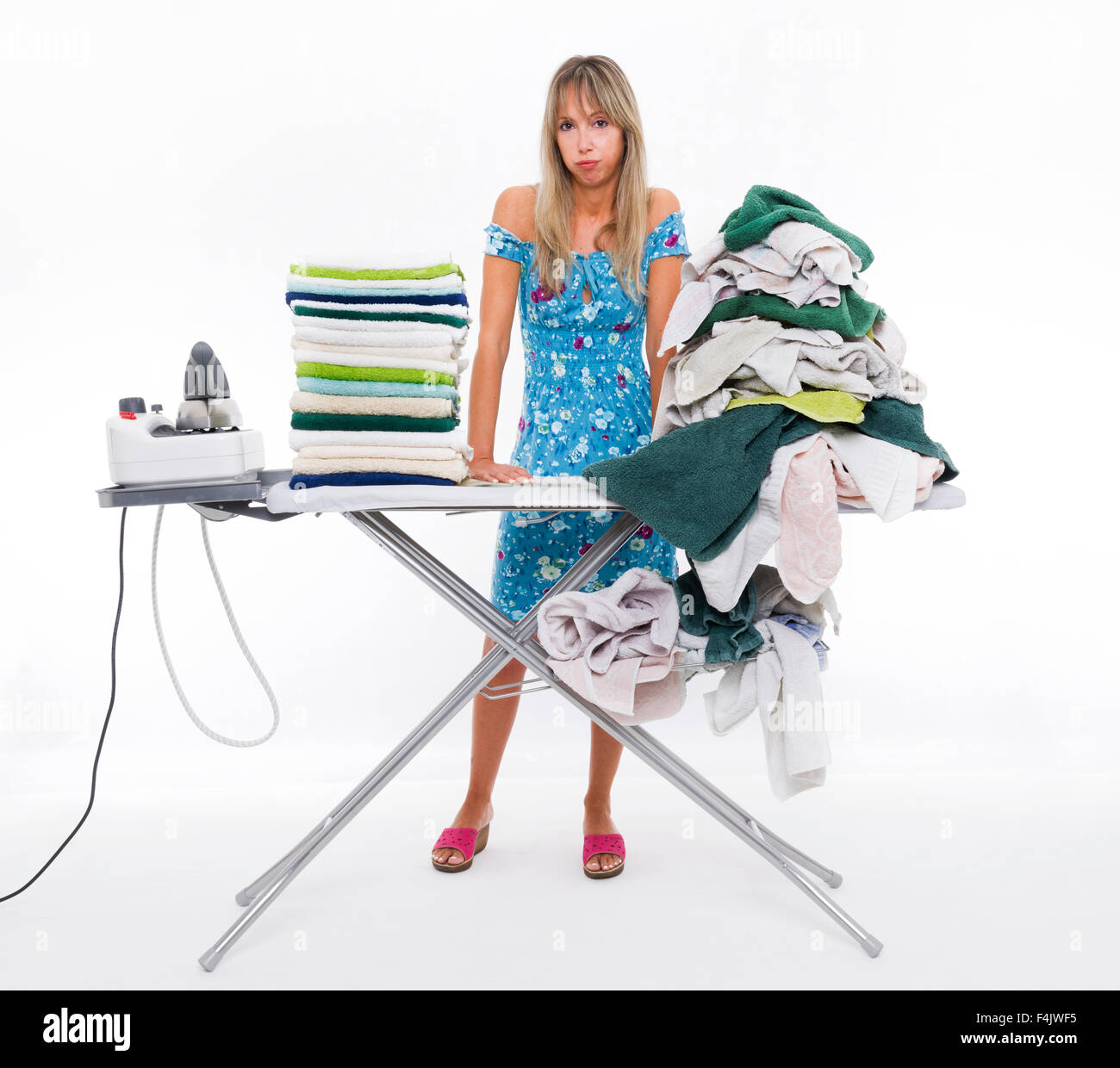 Woman with angry expression ironing on board many clothing - Stock Image