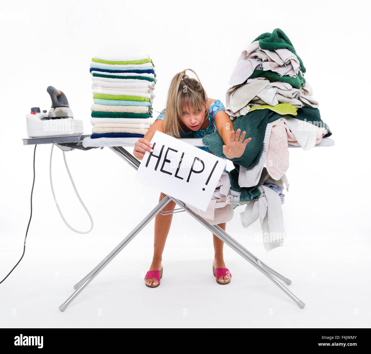 Woman behind a table covered with clothes to be ironed, displays a sign with help - Stock Image