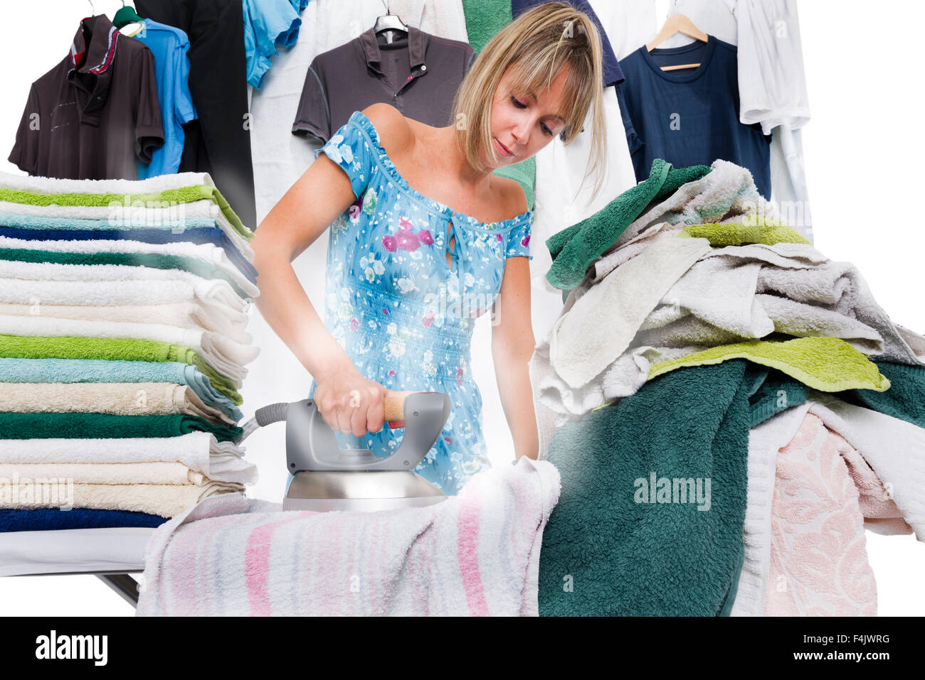 Concentrated woman is ironing many clothes, from the iron out of steam - Stock Image