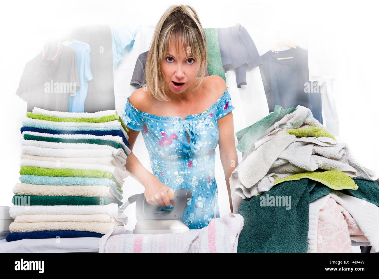 Exhausted woman ironing  many clothes, from the iron out of steam - Stock Image