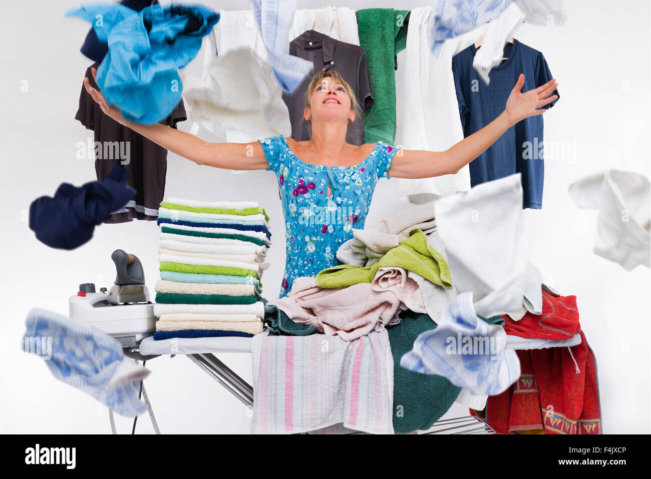 woman behind an ironing board packed with towels iron launches top clothes just ironed - Stock Image