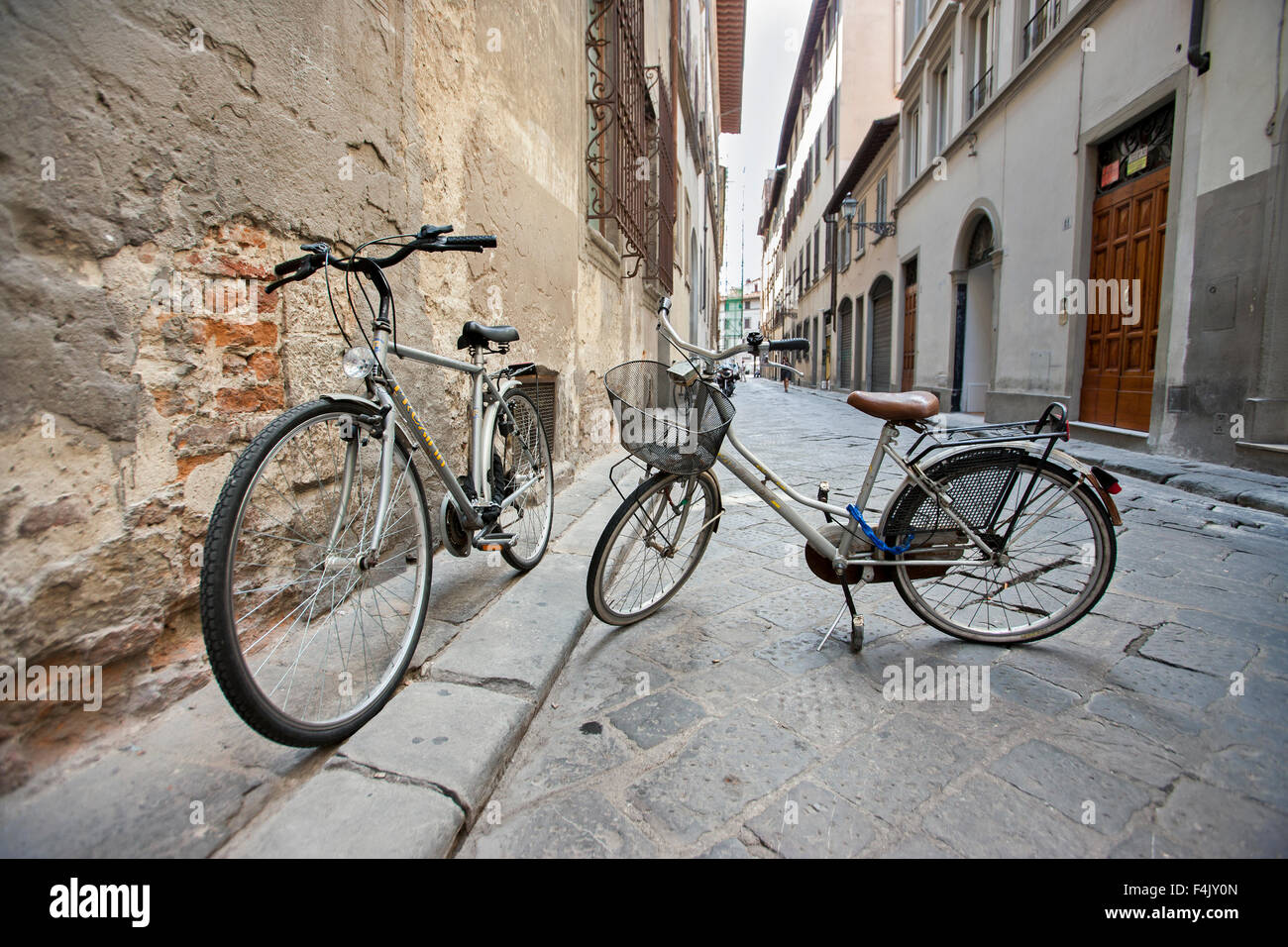 two Bicycles parked on stands in empty street, Florence Italy, - Stock Image