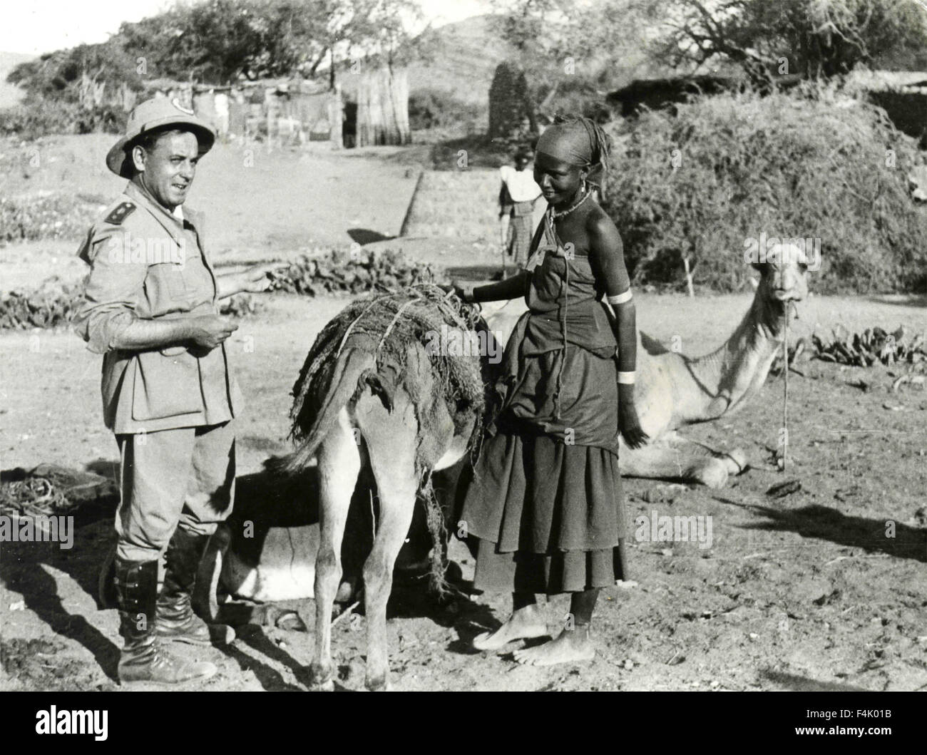 Italian colonial soldier with black woman and camels, Ethiopia - Stock Image