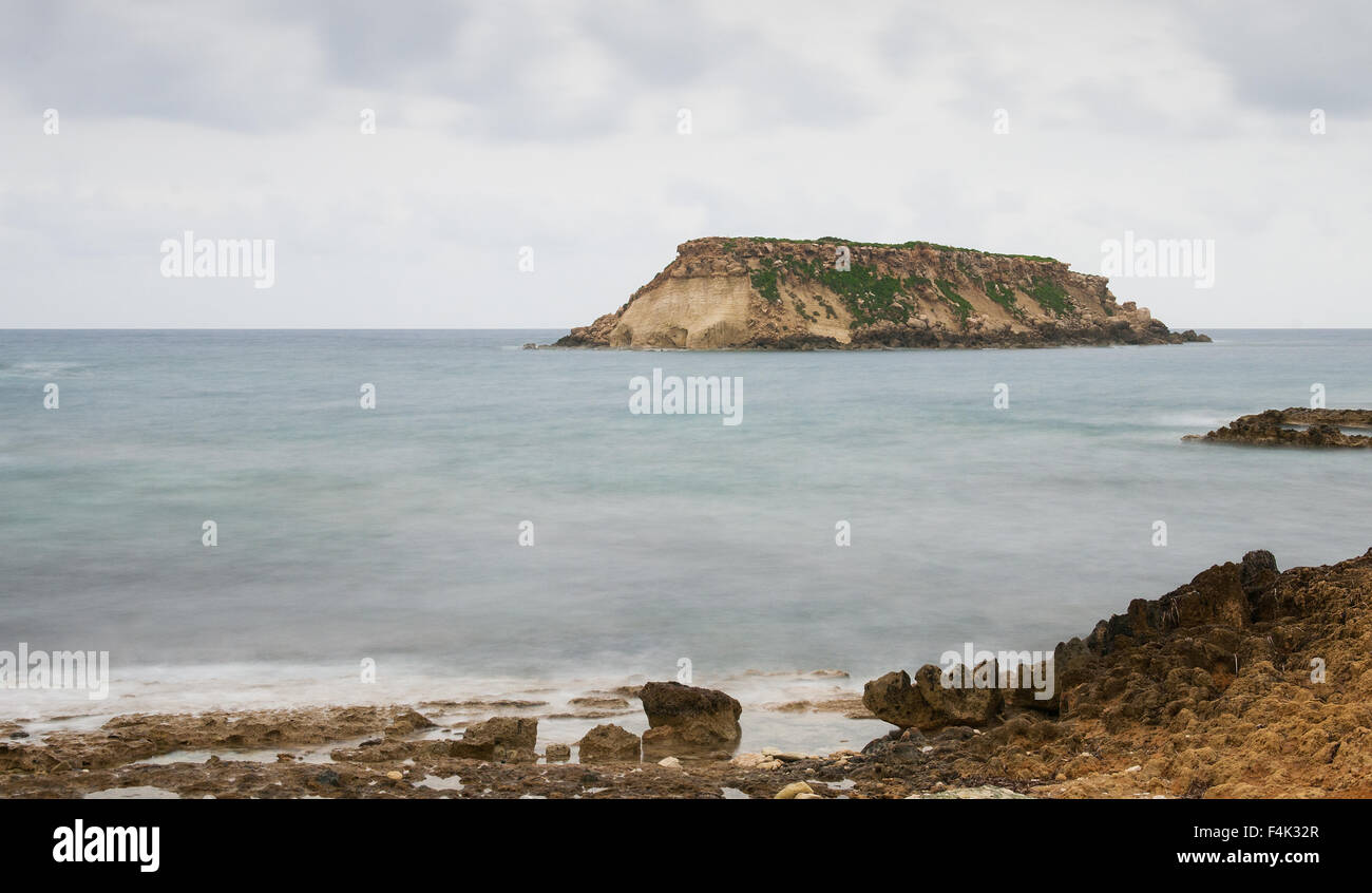 Rocky Seascape with the  small  island of geronisos at st.  georges cape at  Paphos city in Cyprus - Stock Image
