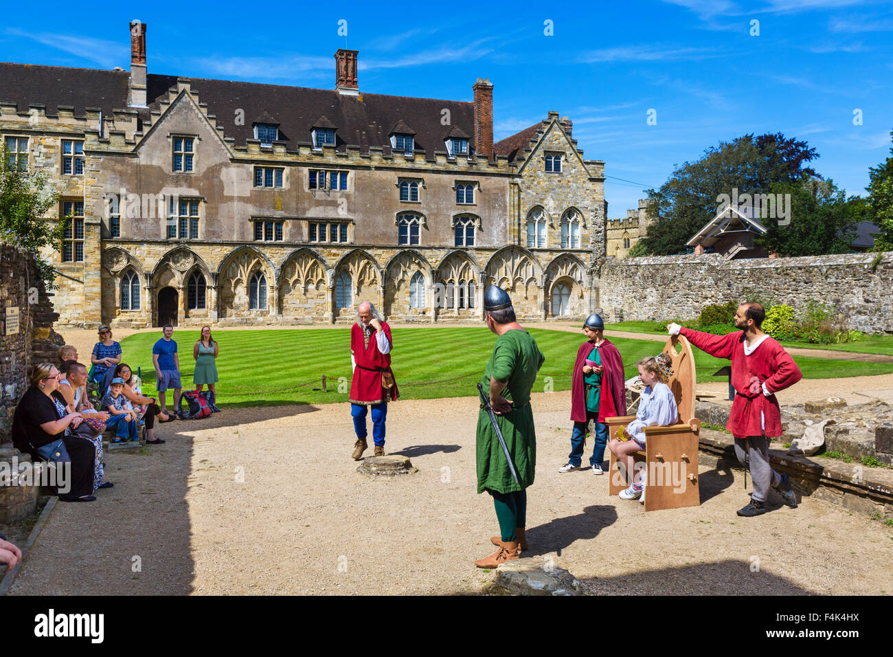 Visitors participatiing in historical re-enactment in front of Abbot's Great Hall (now a school) at Battle Abbey, - Stock Image