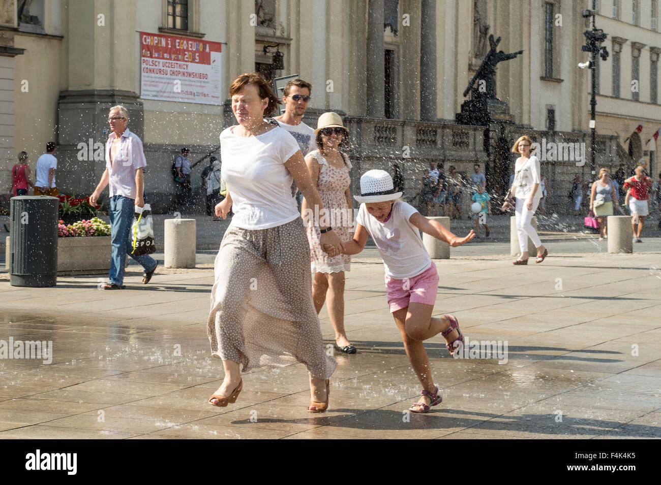 A mother and child run through a sprinkler on a hot day in Warsaw, Poland - Stock Image