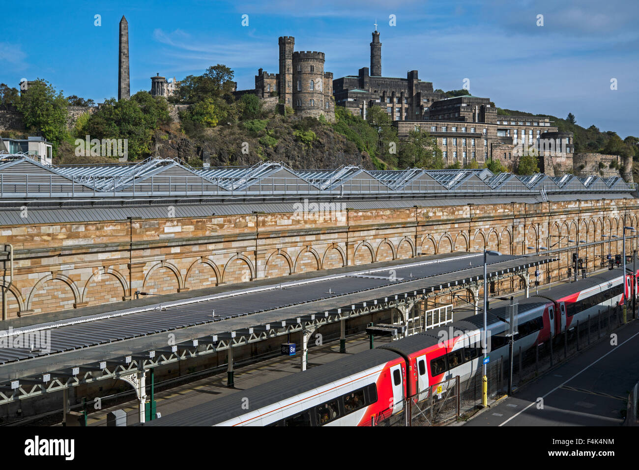 An Virgin train standing at Edinburgh's Waverley Station with Calton Hill in the background. - Stock Image