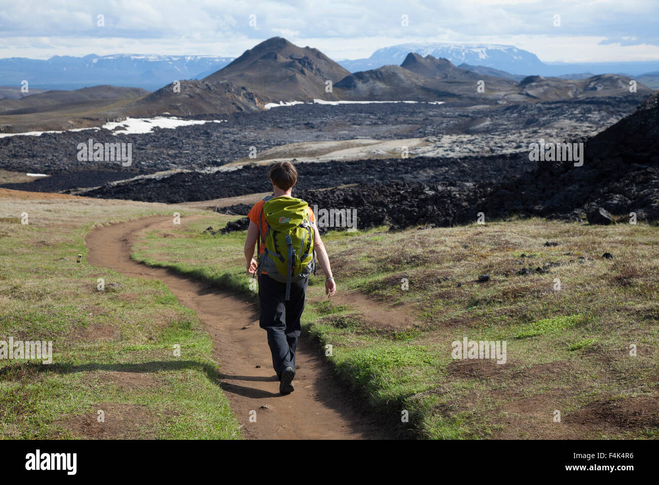Hiker on the trail past Leirhnjukur lava field, Krafla volcanic area, Myvatn, Nordhurland Eystra, Iceland. - Stock Image