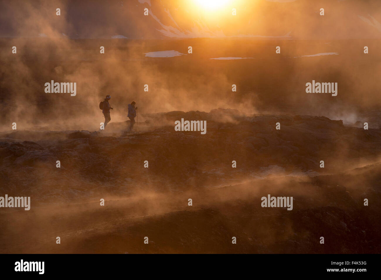 Sunset hikers amid the smouldering lava field at Leirhnjukur, Krafla volcano, Myvatn, Nordhurland Eystra, Iceland. Stock Photo