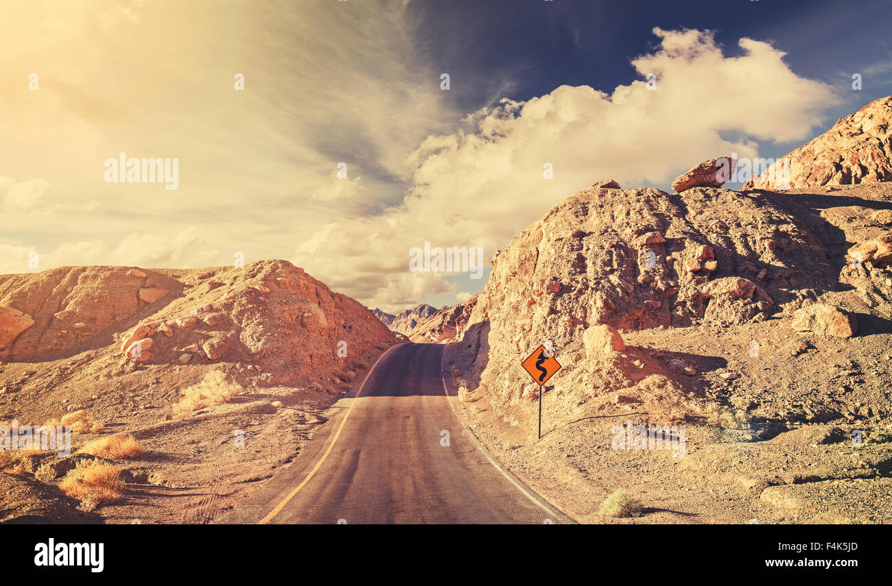 Old film retro stylized rocky desert road, USA. - Stock Image
