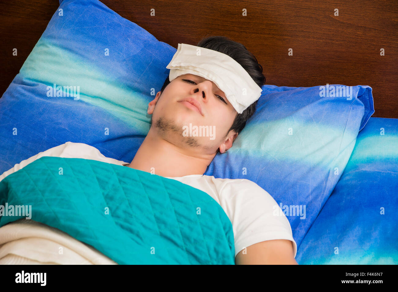 Young handsome sick or unwell man in bed with a flu or fever - Stock Image
