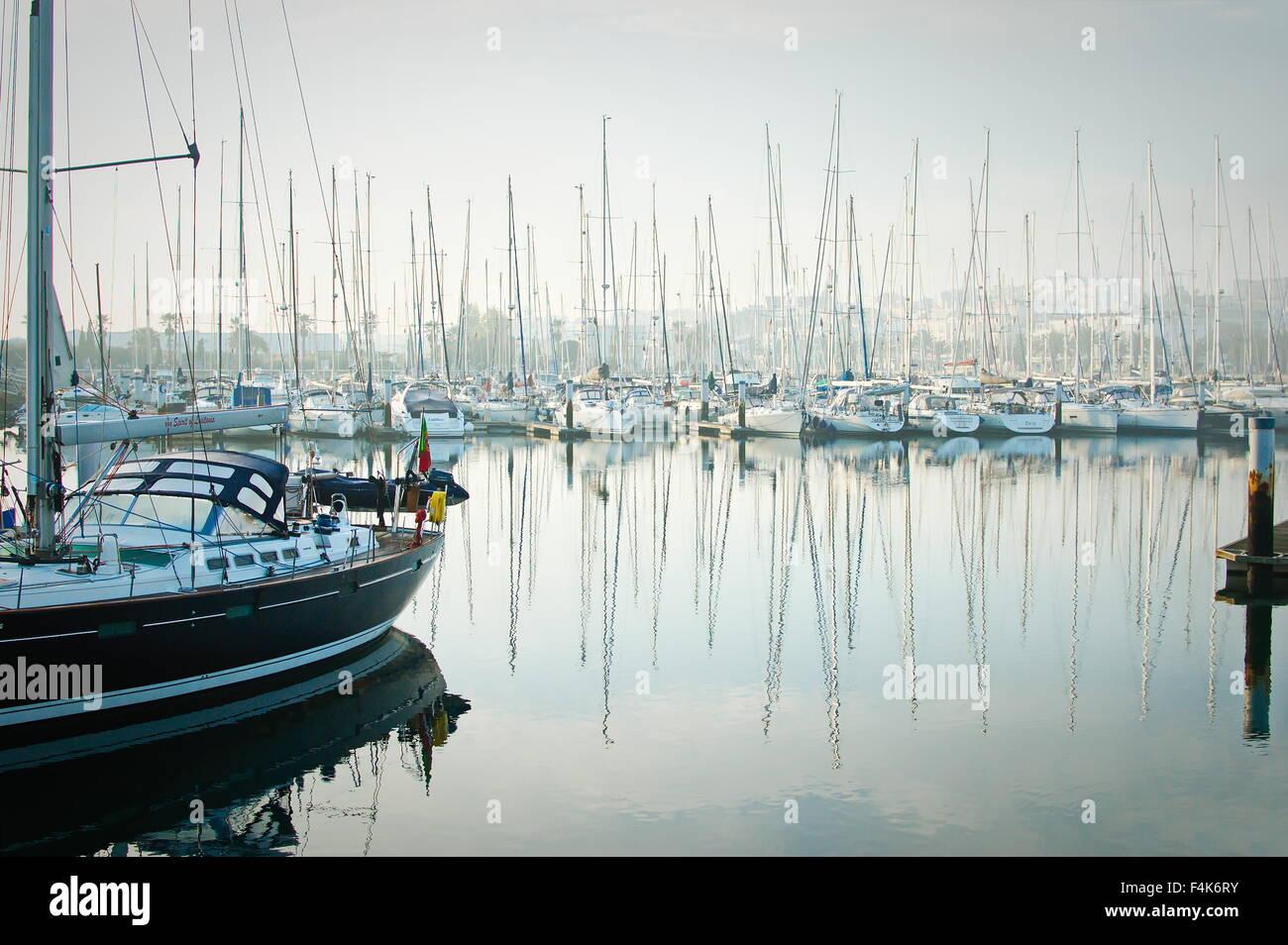Marina de Lagos, Lagos, Algarve, Portugal, 2015-10-16. Boats moored during a dense fog in the marina. - Stock Image