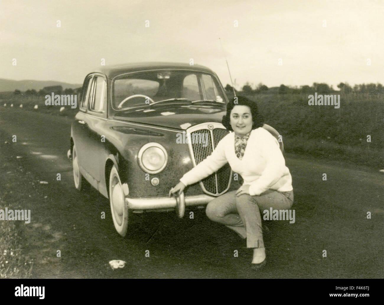 Woman next to a Lancia car, Italy - Stock Image
