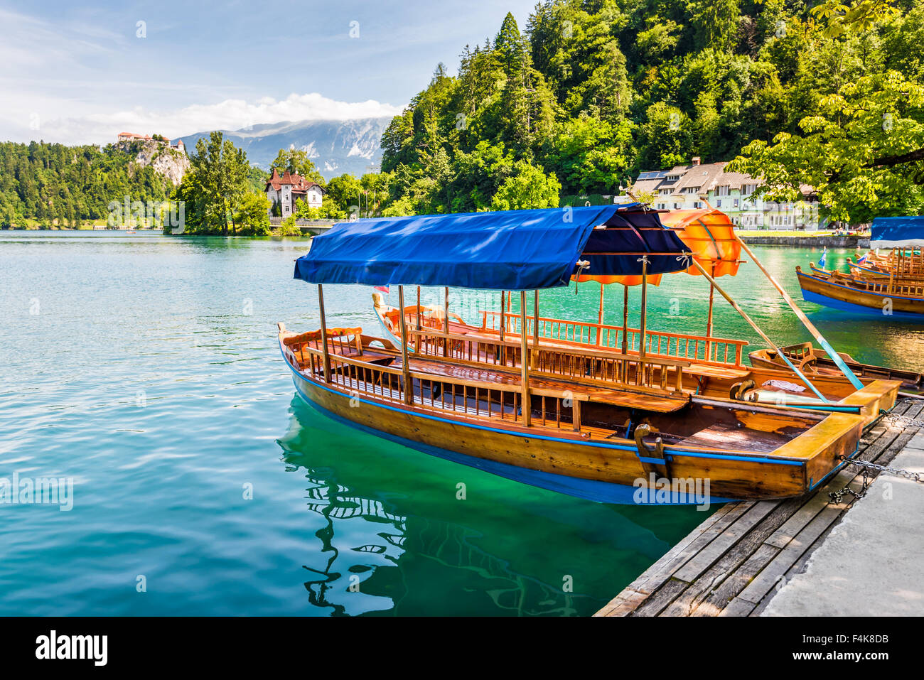 Wooden Tourist Boat on Shore of Bled Lake, Slovenia with Bled Castle in Background - Stock Image