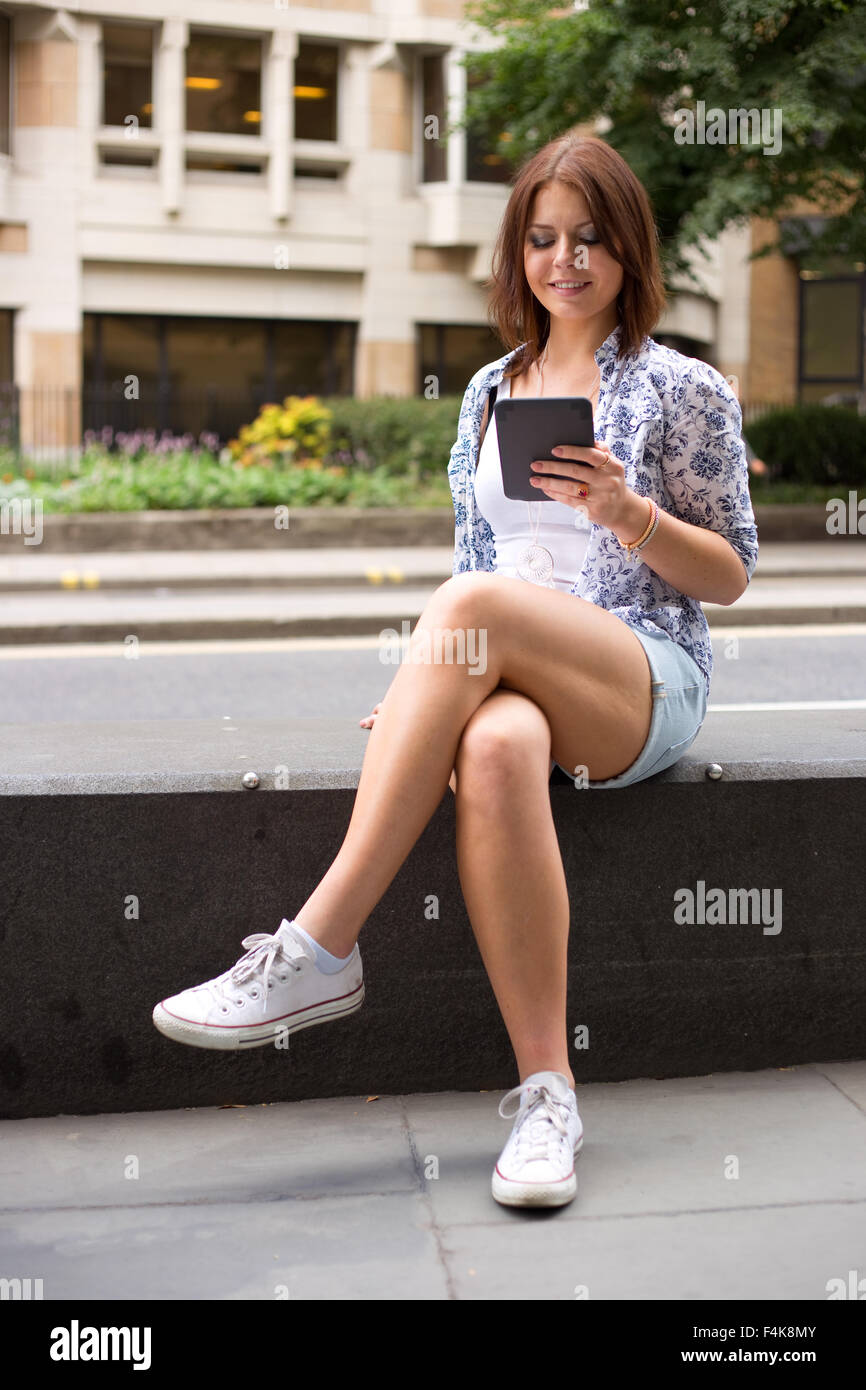 young woman reading an e-book in the street - Stock Image