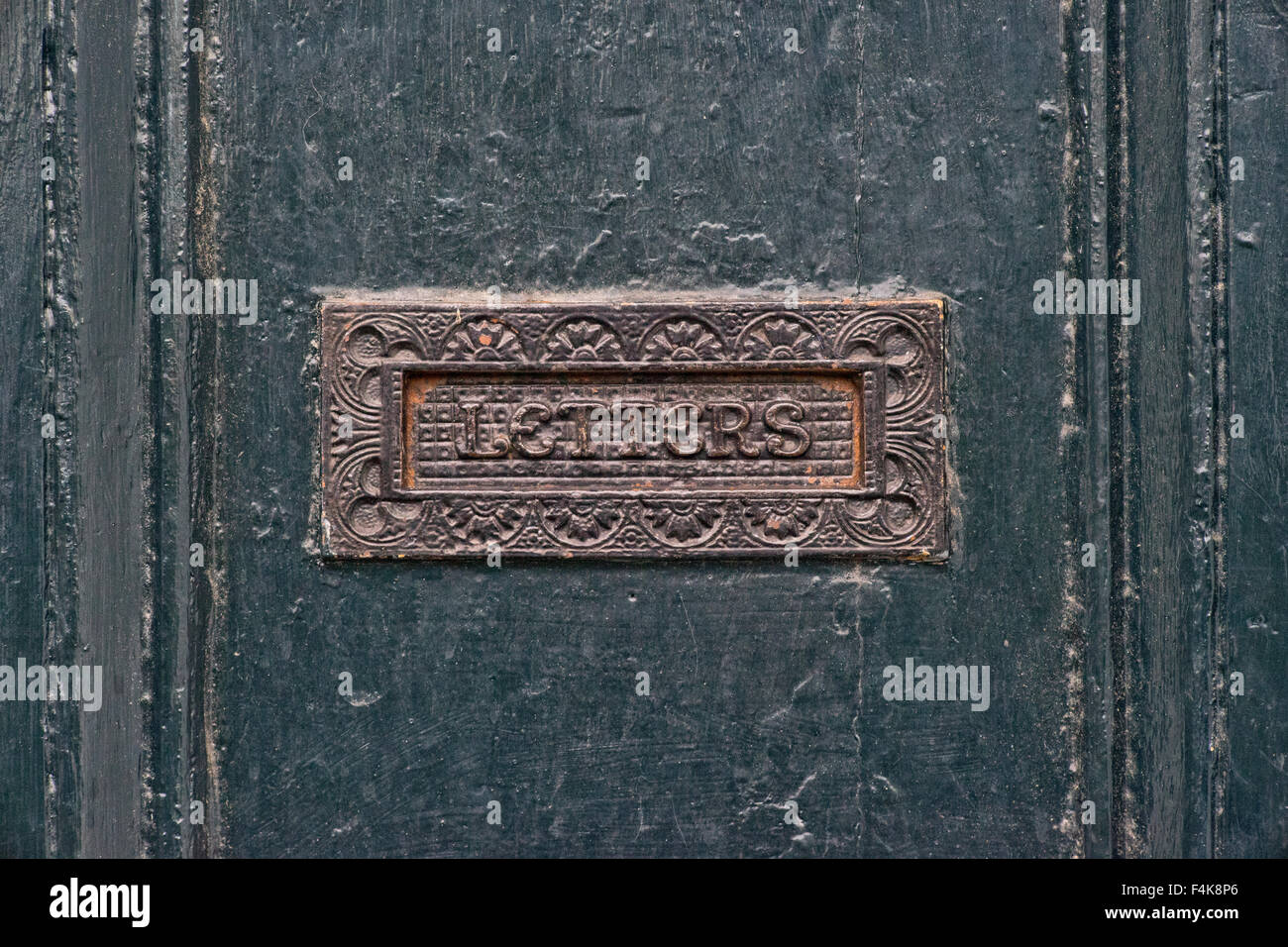 Victorian cast iron Letter Box flap set in old Georgian front door in London - Stock Image