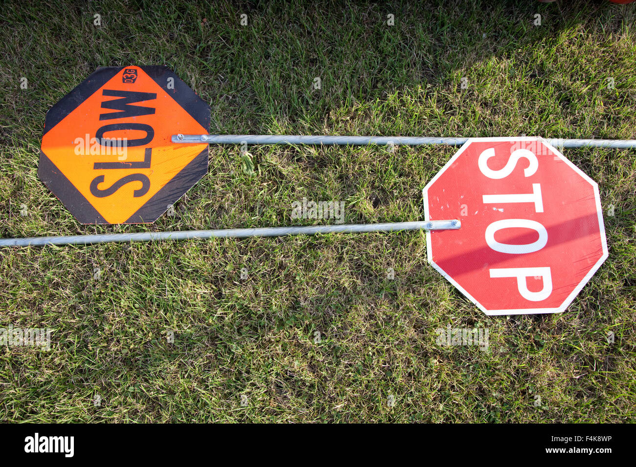 Stop and slow road construction signs lying on the grass
