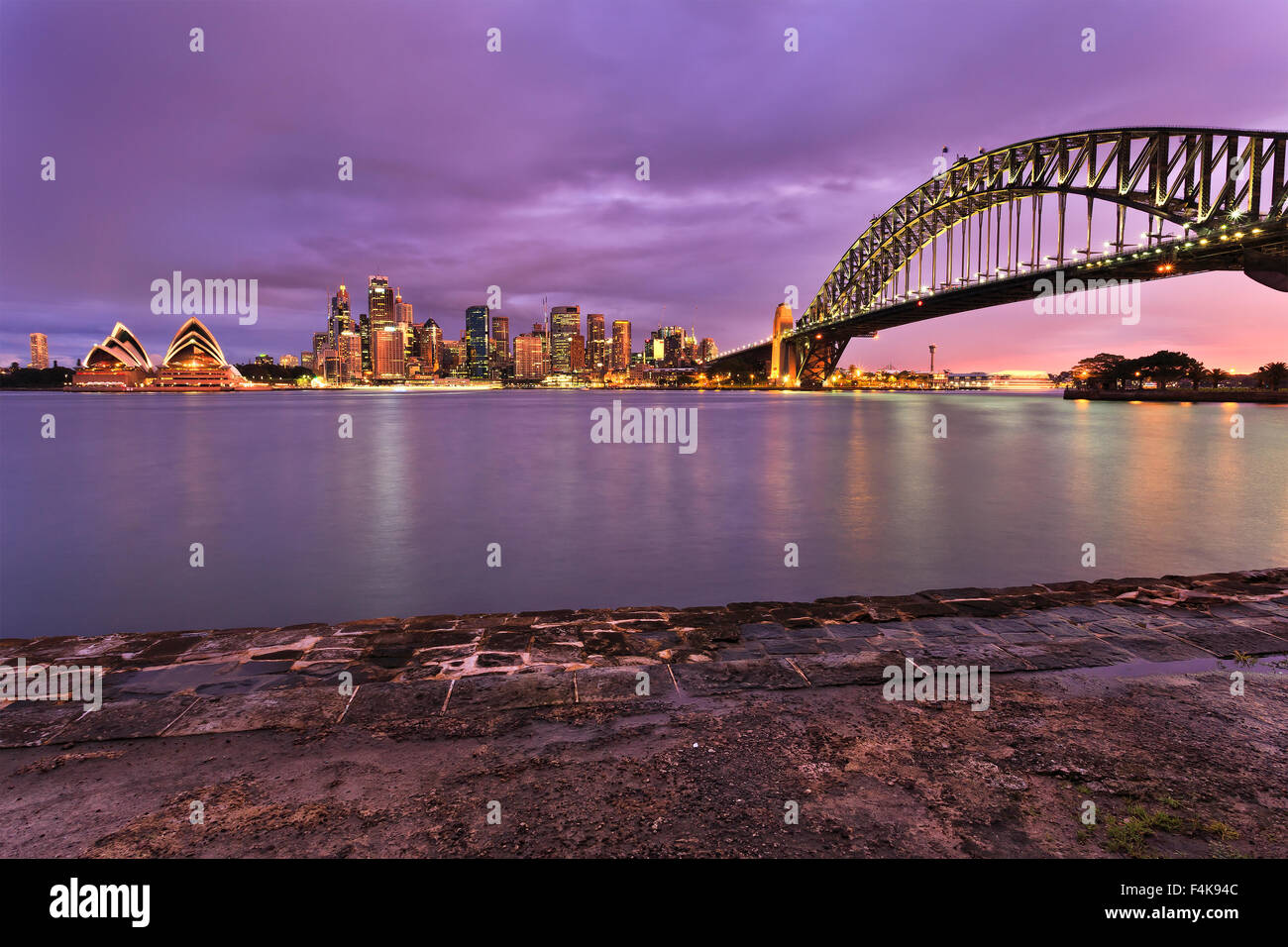 Sydney city CBD landmarks illuminated at sunset and viewed across harbour from Milsons Point. Sydney harbour bridge, - Stock Image