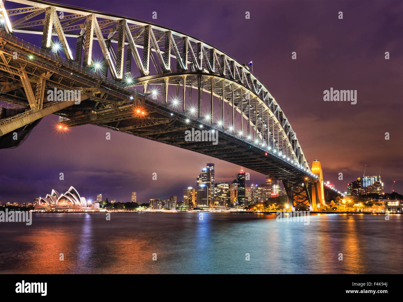 East side of Sydney harbour bridge at sunset with bright illumination of steel arch and columns reflecting in the - Stock Image