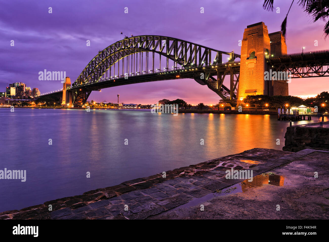 Sydney harbour bridge side view from Milsons point after fresh rain when brightly illuminated bridge arch and column - Stock Image