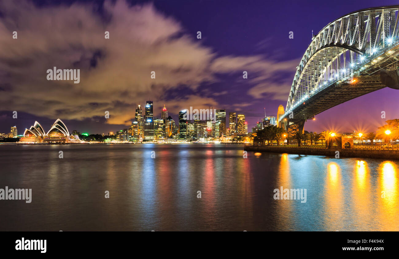 Australia Sydney city CBD cityline across harbour with sky-scrapers, opera and harbour bridge at sunset fully illuminated - Stock Image