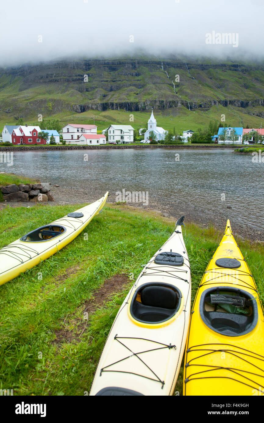 Sea kayaks on the shore of Seydisfjordur, Seydisfjordur village, Austurland, Iceland. - Stock Image