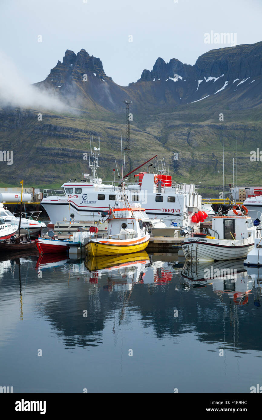 Fishing boats reflected in Stodvarfjordur harbour, Austurland, Iceland. - Stock Image