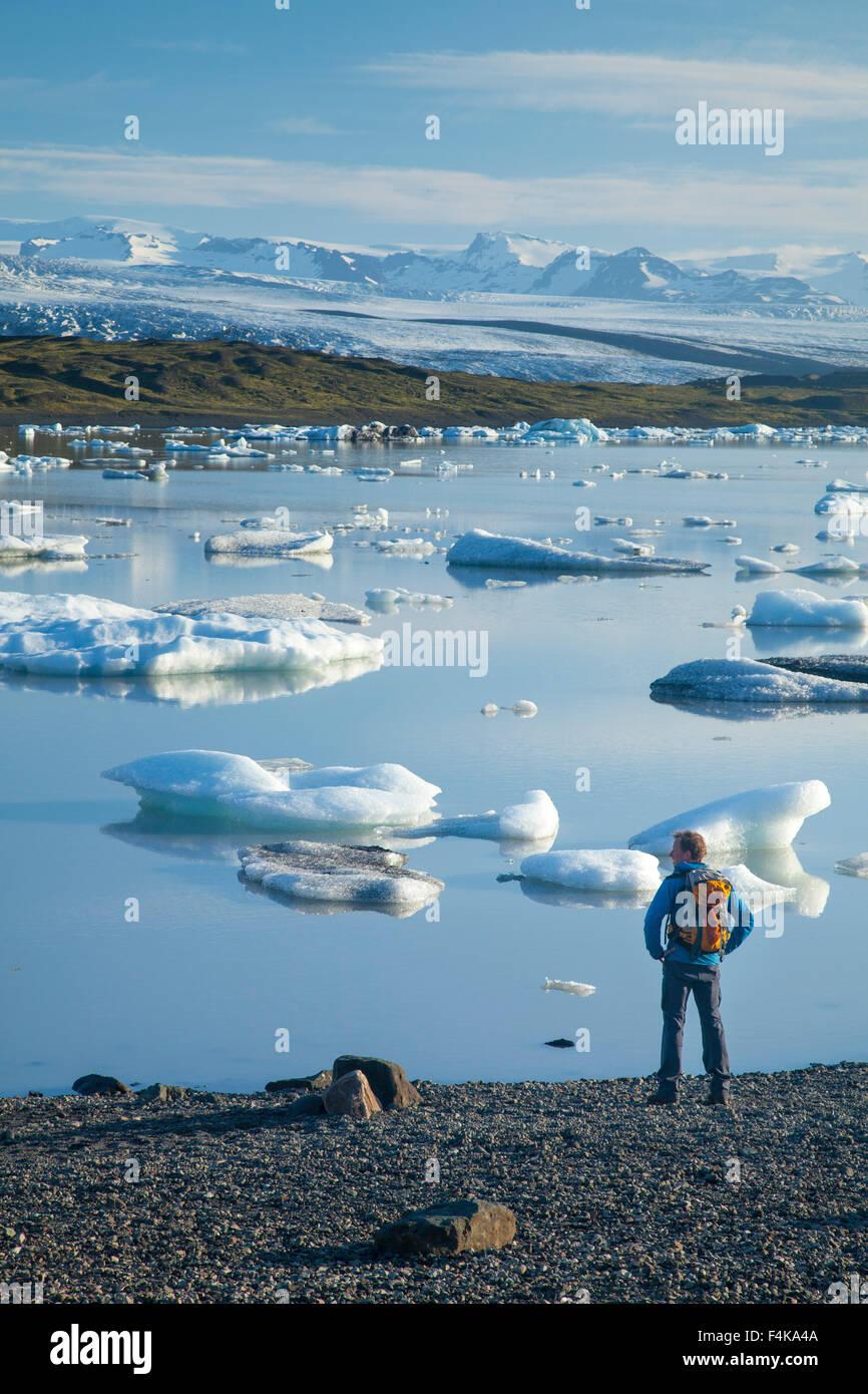 Person beside Fjallsarlon iceberg lagoon, beneath Fjallsjokull glacier. Vatnajokull National Park, Sudhurland, Iceland. - Stock Image