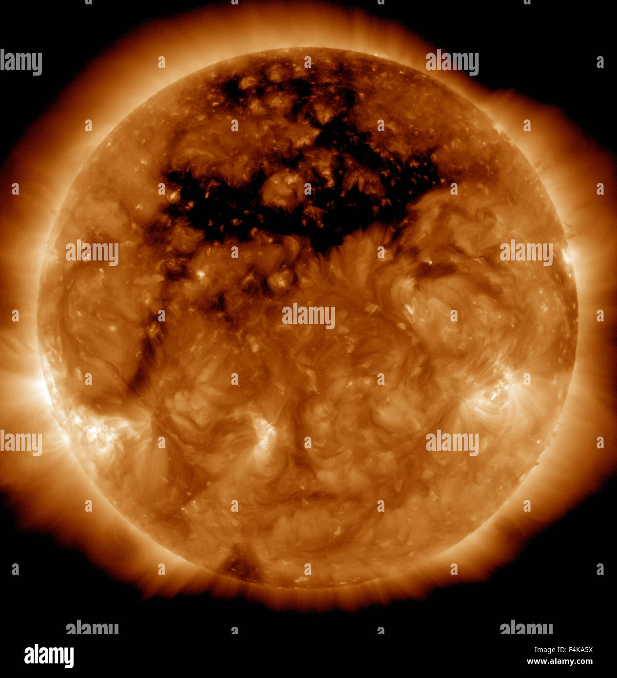 A coronal hole, the dark area across the top of the sun where a region on the sun's magnetic field is open to - Stock Image