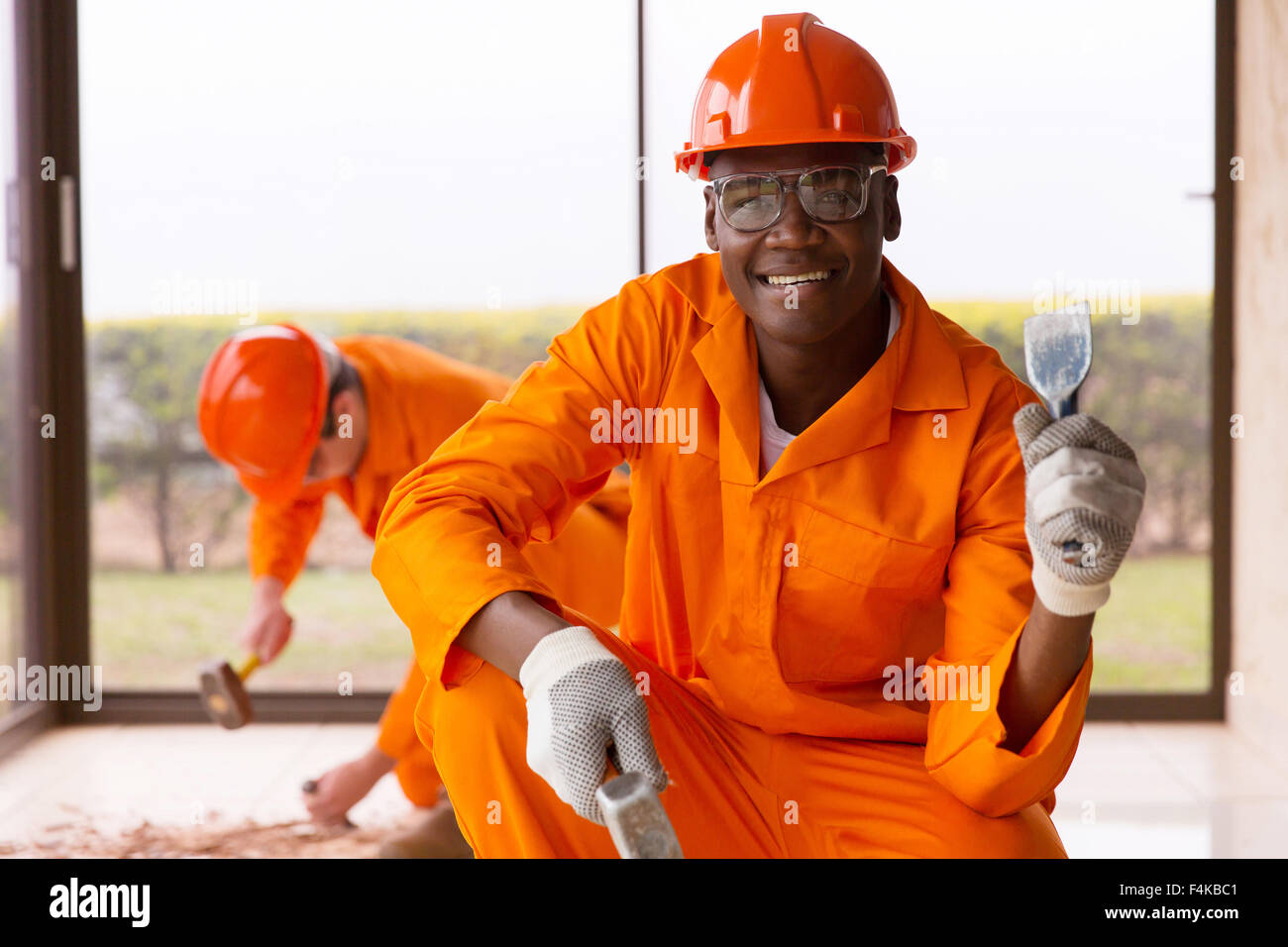 African workman holding chisel and hammer inside house under construction - Stock Image