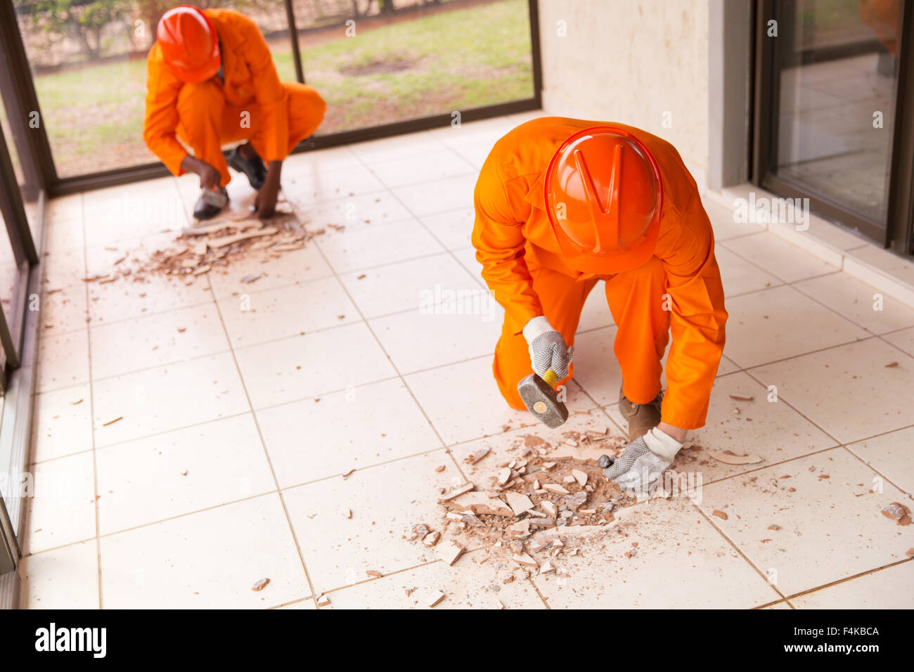 contractors removing old floor tiles using hammer and chisel - Stock Image