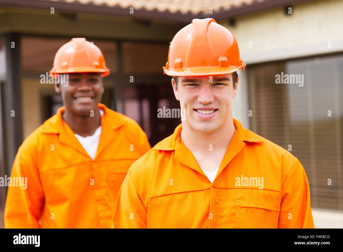 happy young builder and co-worker in front of new house Stock Photo