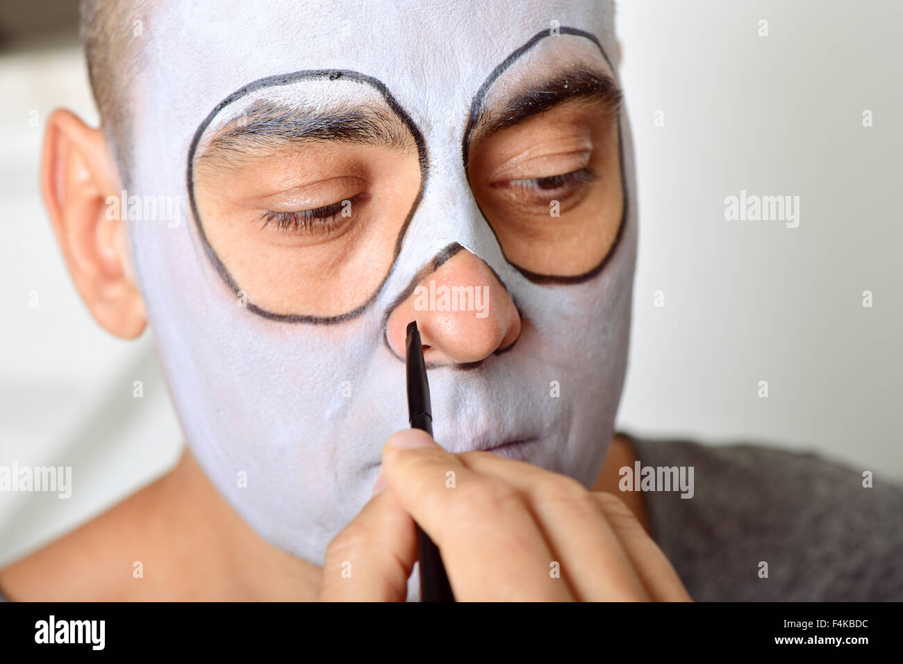 closeup of a young man making up himself to perform a character - Stock Image