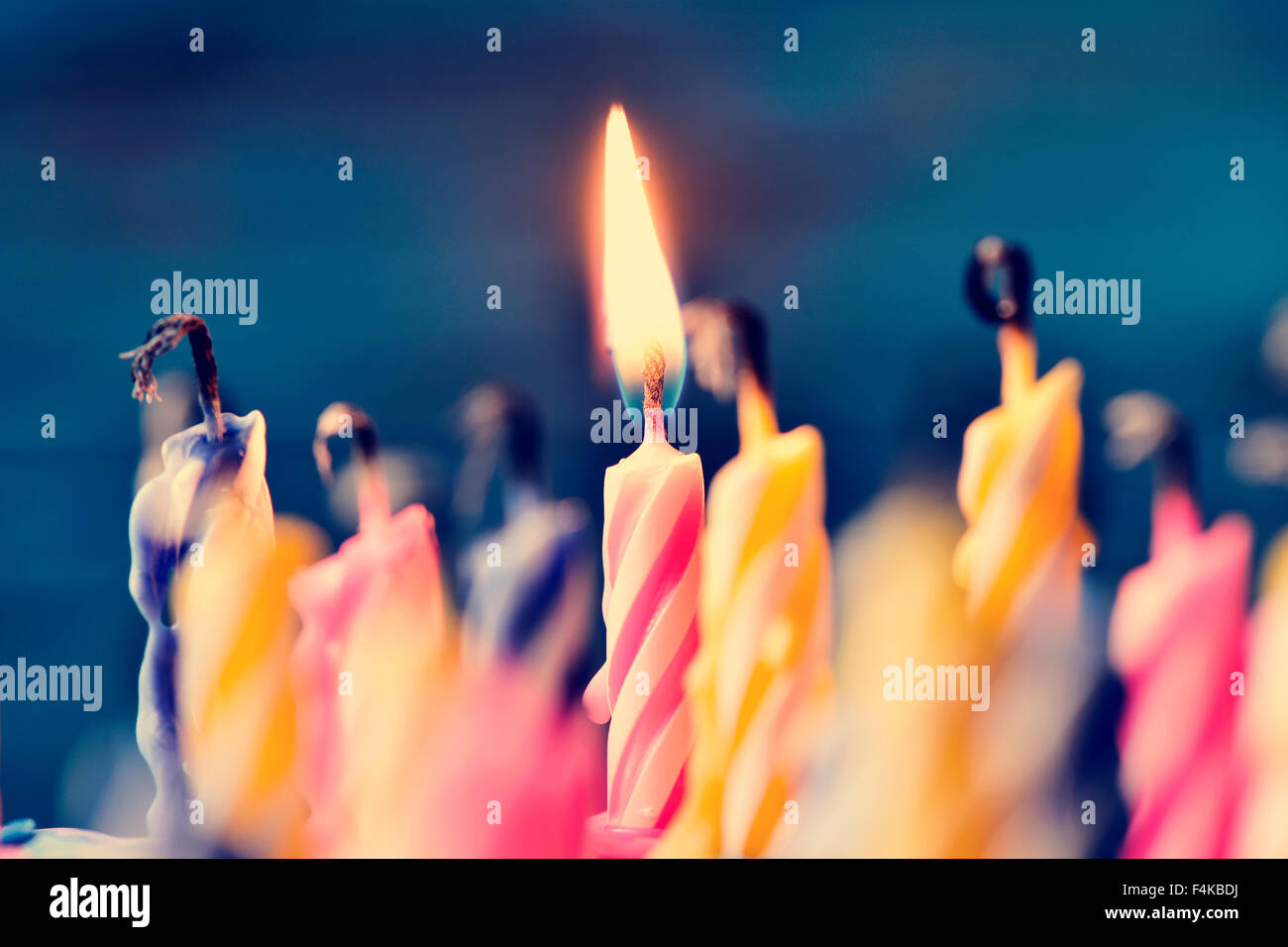 closeup of some unlit candles and just a lit candle after blowing out the cake - Stock Image