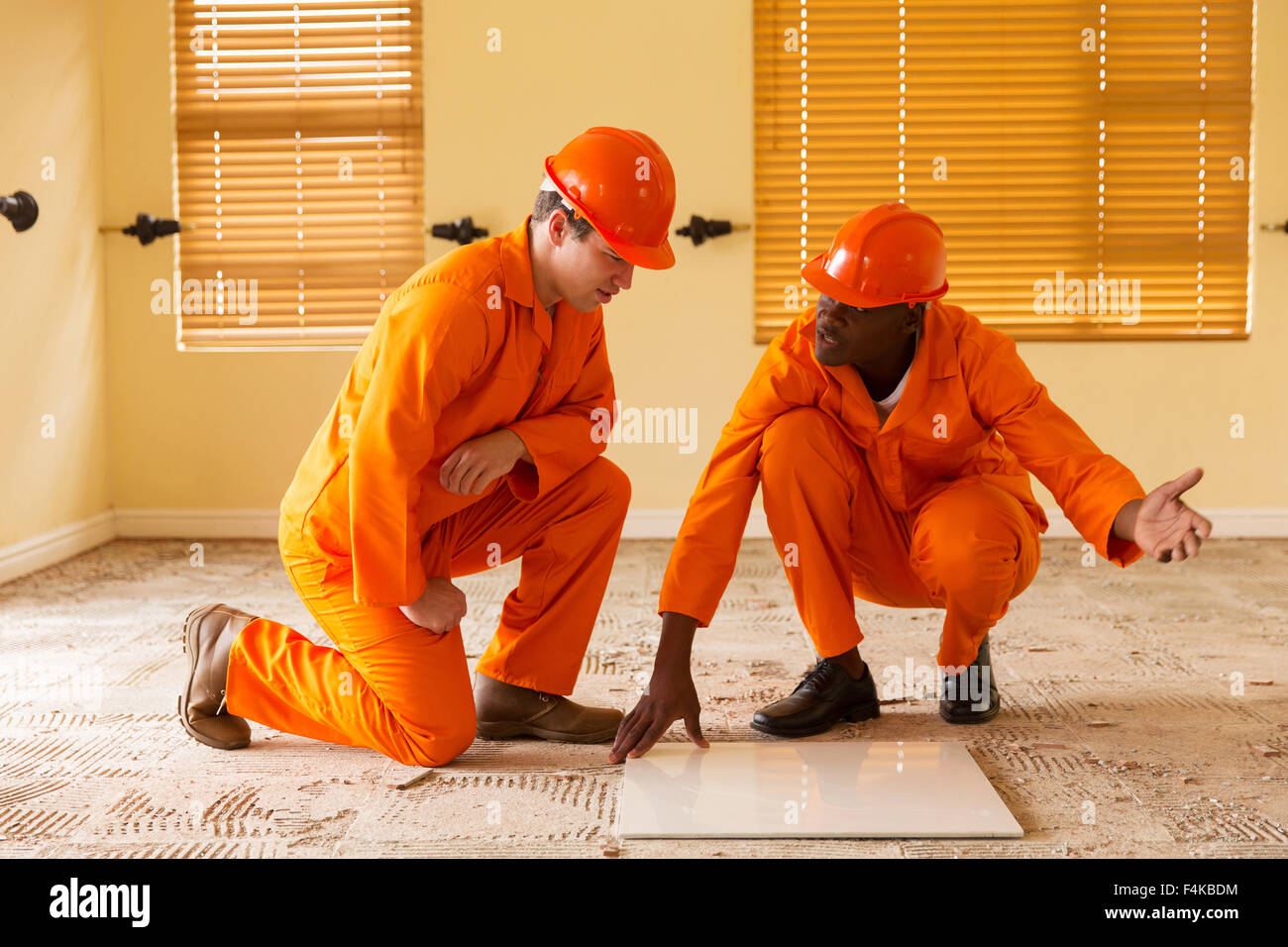 professional construction co-workers discussing floor tiles - Stock Image