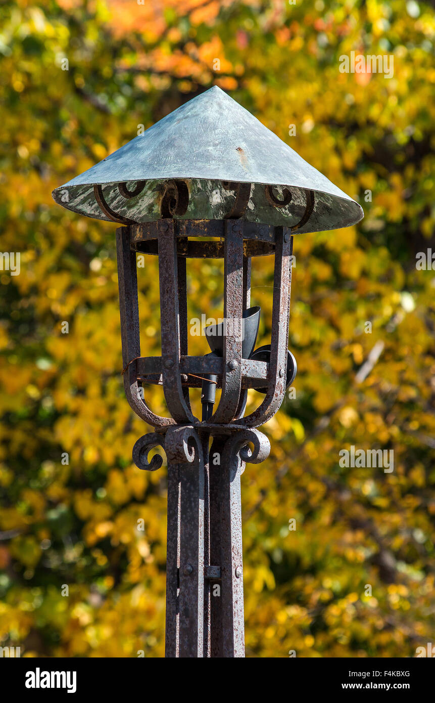Closeup of an antique wrought iron outdoor lamp with fall colors in ...